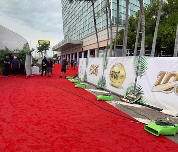 A red carpet with SERVPRO equipment lined up on the carpet in front of a building.