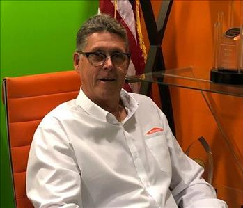 A man sitting in a chair in a Green and Orange room.
