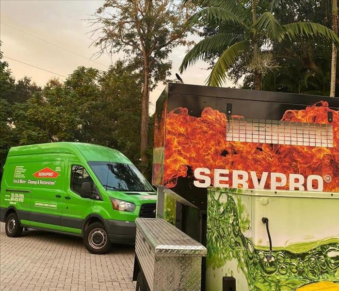 A SERVPRO van and trailer parked in a driveway.