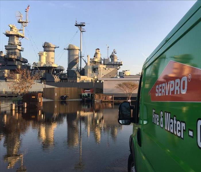 Side View of the Logo of a SERVPRO Van with a Naval Warship in the Background