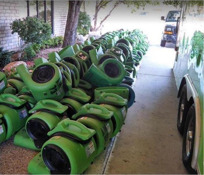 SERVPRO water restoration equipment stacked outside of home