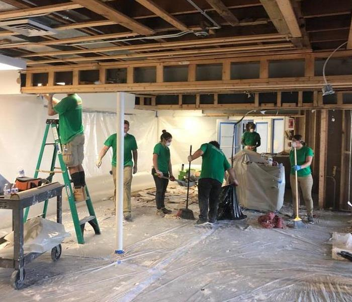 SERVPRO employees working in a room that had been gutted.